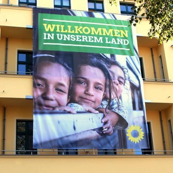 """""""Bienvenidos a nuestro país."""" Banner colgante en la fachada de la central de los verdes en Berlin. Fuente: Fan-Page Bündnis90/die Grünen."""